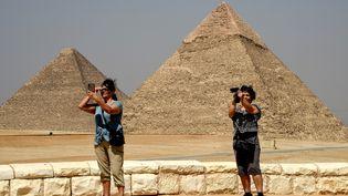 Un selfie pour ces touristes devant la pyramide de Guizèh, au sud-ouest de la capitale égyptienne Le Caire, le 29 mai 2019.  (Mohamed el-Shahed / AFP)