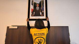 Une militante environnementale décroche un portrait d'Emmanuel Macron, à Saint-Sébastien-sur-Loire (Loire-Atlantique). (LOIC VENANCE / AFP)