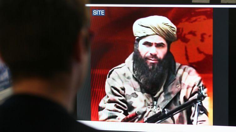 Un homme regarde une photo d'Abdelmalek Droukdel, chef d'Al-Qaida au Maghreb islamique (Aqmi), sur le site du groupe de surveillance américain SITE Intelligence, le 19 novembre 2010 à Paris (photo d'illustration). (THOMAS COEX / AFP)