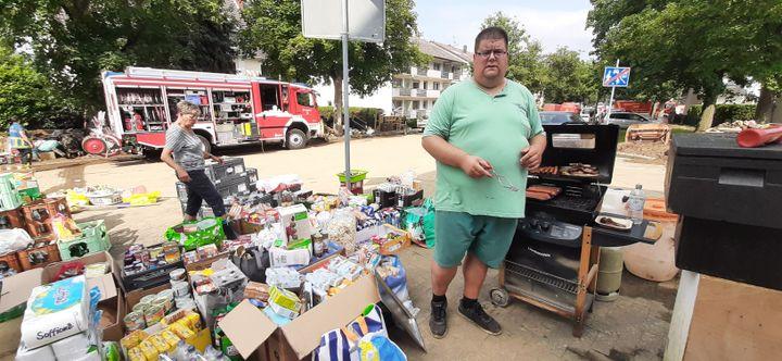 Mario, un habitant de Sinzig dont le barbecue a été miraculeusement épargné par les inondations, fait cuire des saucisses pour tous ses voisins durement touchés. Ils peuvent également venir chercher des vivres. (SEBASTIEN BAER / FRANCEINFO / RADIO FRANCE)