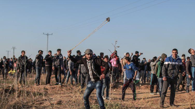Des Palestiniens lancent des pierres contre les forces de sécurité israéliennes lors d'un rassemblement de protestation, à Gaza, le 8 décembre 2017. (ALI JADALLAH / AFP)