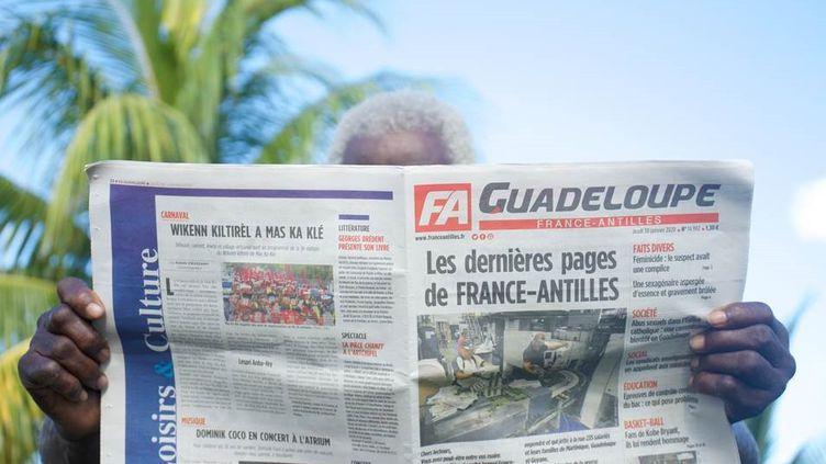 """Le dernier numéro de """"France-Antilles"""", lu par un homme à Pointe-à-Pitre en Guadeloupe, le 30 janvier 2020. (CEDRIK-ISHAM CALVADOS / AFP)"""