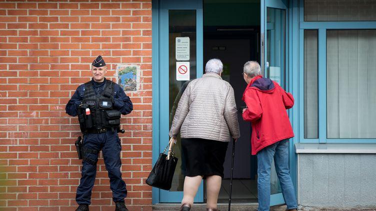 Un policier devant un bureau de vote d'Hénin-Beaumont (Pas-de-Calais), le 23 avril 2017, jour du premier tour de l'élection présidentielle. (KAY NIETFELD / AFP)