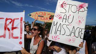 Des jeunes ont manifesté leur colère contre la prolifération des requins au large de la Réunion, mercredi 15 avril, lors d'une marche d'hommage au jeune Elio, surfeur de 13 ans happé par un squale trois jours plus tôt. (RICHARD BOUHET / AFP)