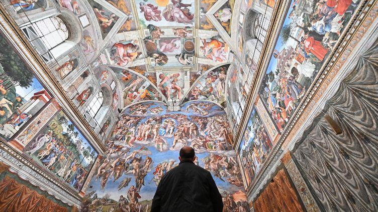 Un homme visite la Chapelle Sixtine le 1er février 2021, jour de réouverture des musées du Vatican. Décoré de fresques réalisées par Michel-Ange au XVIe siècle, le célèbre plafond de la Chapelle a été dépoussiéré durant le confinement dû à la pandémie de Covid-19. (ANDREAS SOLARO / AFP)
