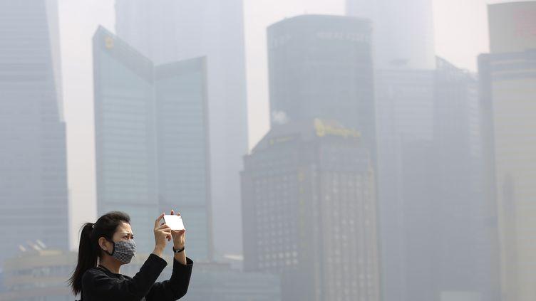 Une femme prend une photodans la ville deShanghai (Chine) polluée, le 7 mars 2016. (ALY SONG / REUTERS)