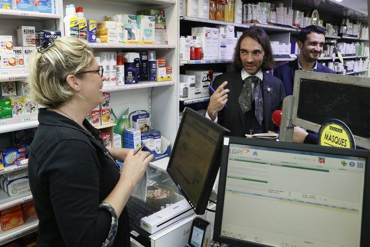 Le mathématicien Cédric Villani, candidats aux élections législatives dans l'Essonne, discute avec une pharmacienne d'Orsay, le 12 mai 2017. (THOMAS SAMSON / AFP)
