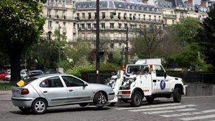 Une voiture est emmenée par la fourrière, le 2 mai 2013, dans le 16e arrondissement de Paris. ( MAXPPP)