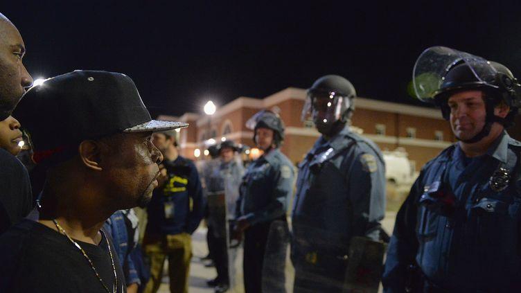 Des manifestants font face à des policiers devant le siège de la police de Ferguson (Missouri), le 11 mars 2015. (MICHAEL B. THOMAS / GETTY IMAGES NORTH AMERICA / AFP)