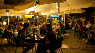 Des clients dînent et boivent un verre en terrasse, à Barcelone (Espagne), le10 juillet 2021. (DAVIDE BONALDO / CONTROLUCE / AFP)