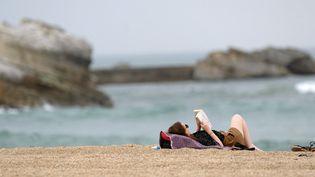 Une femme lit au bord de la plage à Biarritz, en avril 2015.   (IROZ GAIZKA / AFP)