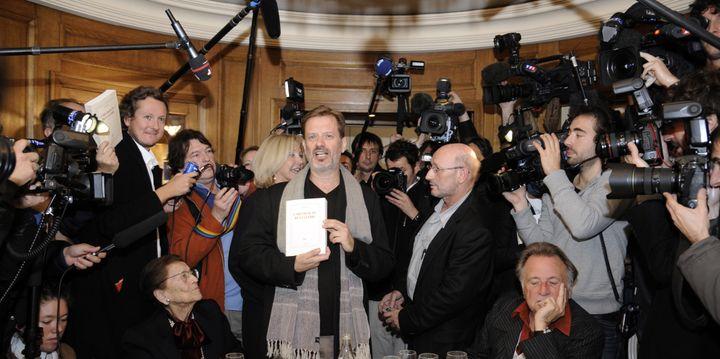 """Alexi Jenni pose avec avec son livre """"L'Art français de la guerre"""" alors qu'il vient d'être récompensé du prix Goncourt, le 2 novembre 2011 au restaurant Drouant, à Paris. (BERTRAND GUAY / AFP)"""