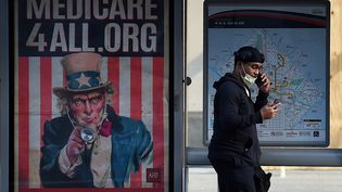 """Un Américain passe devant une affiche """"Medicare for All"""" à Washington, DC, le 3 juin 2020. (OLIVIER DOULIERY / AFP)"""