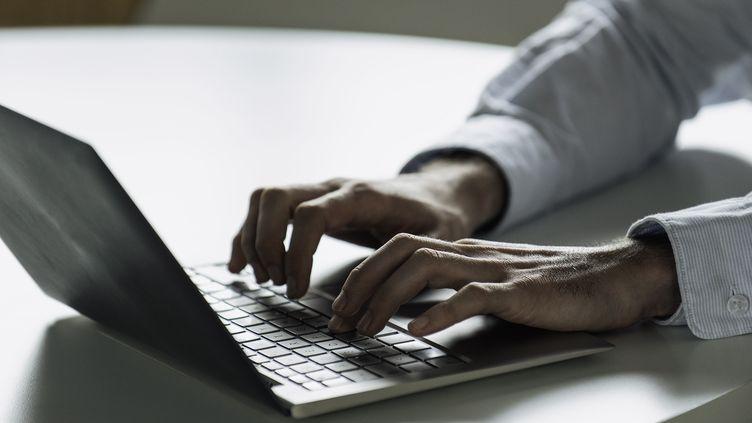 Un jeune homme et son ordinateur. Photo d'illustration. (ERIC AUDRAS / MAXPPP)