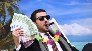 Un militant d'Oxfam se met en scène pour dénoncer les paradis fiscaux, le 5 décembre 2017, à Bruxelles. (EMMANUEL DUNAND / AFP)