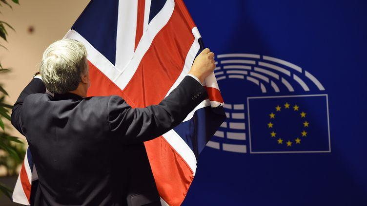 Un homme installe un drapeau britannique avant l'arrivée du Premier ministre David Cameron, le 16 février 2016, au Parlement européen, à Bruxelles (Belgique). (EMMANUEL DUNAND / AFP)
