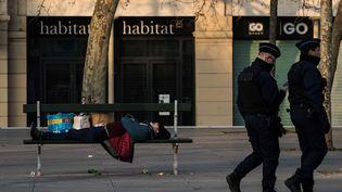 Des policiers passant devant un SDF endormi sur un banc, à Paris. (JOEL SAGET / AFP)