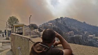 En Algérie, un homme regarde la fumée s'échapper d'un incendie de forêt dans les collines boisées de la Kabylie, à l'est de la capitale Alger, le 10 août 2021. (RYAD KRAMDI / AFP)