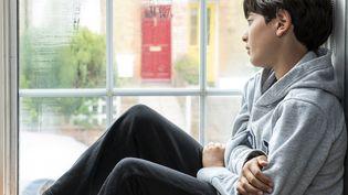 Un adolescent assis dans sa chambre regarde par la fenêtre, pendant la crise du coronavirus. (Photo d'illustration) (BONFANTI DIEGO / CULTURA CREATIVE / AFP)