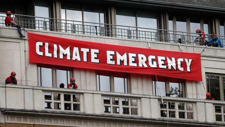 Des militants écologistes déploient une banderole à l'extérieur du siège de la compagnie British Petroleum, lundi 20 mai 2019 à Londres (Royaume-Uni). (ADRIAN DENNIS / AFP)