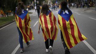 """Trois jeunes femmes portent l'""""estelada"""", le drapeau catalan pro-indépendance, à Barcelone (Espagne), le 28 septembre 2017, lors d'une manifestation en faveur du référendum d'autodétermination. (PAU BARRENA / AFP)"""