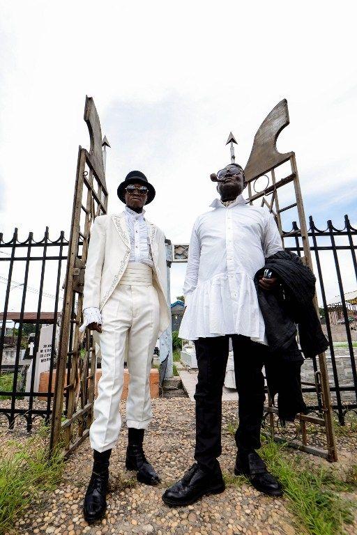 """Mwetu (gauche) et Mozar, deux sapeurs membres du mouvement """"La Sape"""", au cimetière de Gombe en février 2014  (JUNIOR D. KANNAH / AFP)"""