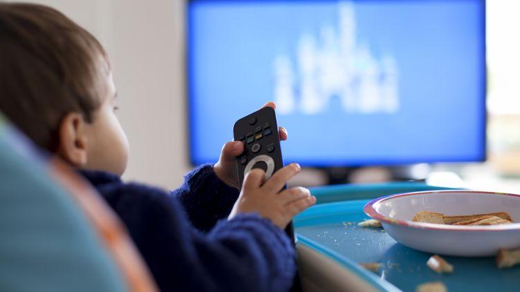 Un enfant mange devant la télévision. Photo d'illustration. (THANASIS ZOVOILIS / MOMENT OPEN / GETTY IMAGES)