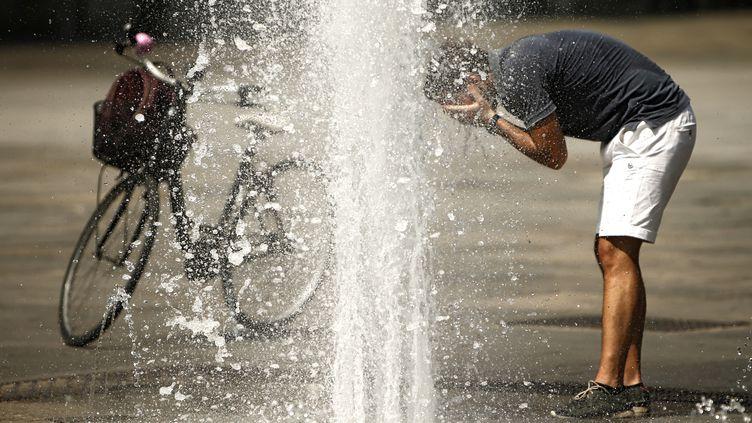 Un homme se rafraîchit près d'une fontaine sur la place Castello de Turin, en Italie,mercredi 2 août 2017. (MARCO BERTORELLO / AFP)