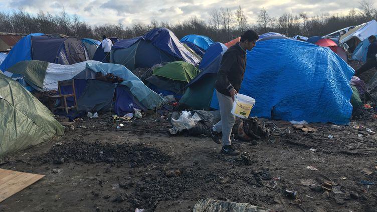 Un migrant aménage un espace pour installer une tente dans le camp de Grande-Synthe (Nord), mardi 29 décembre 2015. (F. MAGNENOU / FRANCETV INFO)