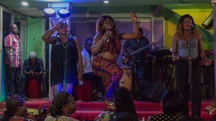 Accompagnée d'une chorale et d'un groupe, Olivia Beyene interprète un morceau de bikutsi et danse sur la scène du cabaret Québec à Yaoundé, le 2 octobre 2019. (STR / AFP)