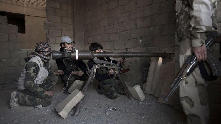 Des rebelles syriens en faction dans un immeuble à Deir Ezzor, dans l'est de la Syrie, le 27 février 2013. (ZAC BAILLIE / AFP)