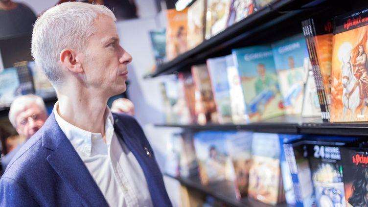 Le ministre de la Culture Franck Riester devant des bandes dessinées, lors de la 46e édition du festival international de la BD d'Angoulême, le 26 janvier 2019. (YOHAN BONNET / AFP)