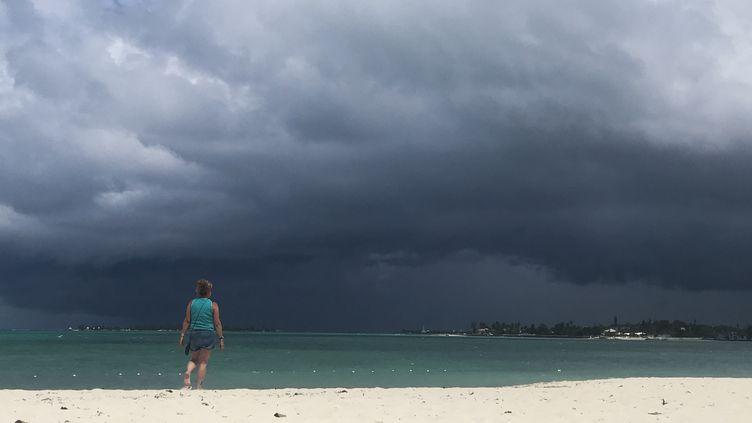Une femme marche sur la plage de Nassau, aux Bahamas, alors qu'une tempête arrive, le 12 septembre 2019. (ANDREW CABALLERO-REYNOLDS / AFP)