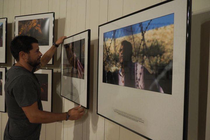 Un homme prépare l'exposition du photographe Guillermo Arias sur les migrants d'Amérique latine. (RAYMOND ROIG / AFP)