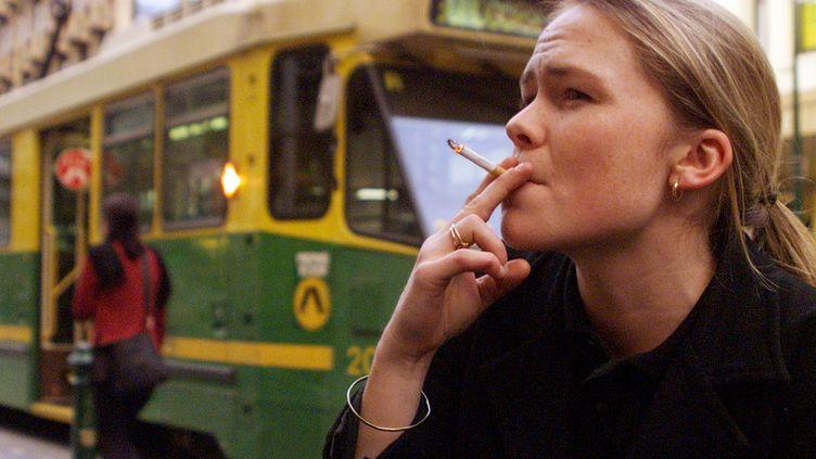 Une Australienne fume une cigarette à Melbourne (Australie), le 21 mai 1999. (WILL BURGESS / REUTERS)