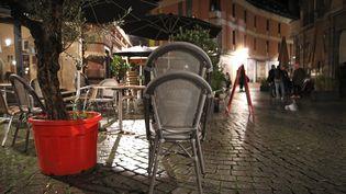 Des cafetiers rangent leur mobilier de terrasse dans le centre ville de Strasbourg le 24 octobre peu avant minuit l'heure de mise en application du couvre-feu. (JEAN-MARC LOOS / MAXPPP)