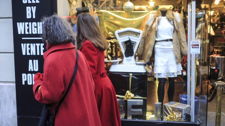 Deux passantes devant une vitrine de boutique décorée pour les fêtes de fin d'année. (AURELIEN MORISSARD / MAXPPP)