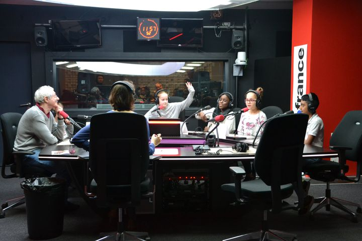 Des écoliers posent leurs questions au micro de franceinfo junior, lors d'un atelier réalisé depuis un studio de Radio France. (ESTELLE FAURE / FRANCEINFO - RADIOFRANCE)