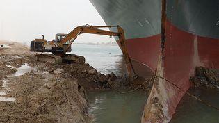 Unepelleteuse essaie de dégager le navire Evergreen encastré dans le canal de Suez (Egypte), le 25 mars 2021. (AFP PHOTO / HO / SUEZ CANAL)
