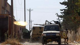 Un combattant loyal au Gouvernement libyen d'union nationale (GNA), reconnu internationalement, tire avec une arme montée sur un camion lors d'affrontements avec les forces fidèles à l'homme fort Khalifa Haftar à Ain Zara, dans la banlieue de Tripoli, le 7 septembre 2019. (MAHMUD TURKIA / AFP)
