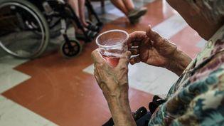 Une personne âgée tient un verre d'eau dans une maison de retraite (TARIS PHILIPPE / MAXPPP)