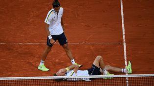 La joie de Pierre-Hugues Herbert (debout) et de Nicolas Mahut (au sol) après leur victoire en finale du tournoi de doubles de Roland-Garros 2021, le 12 juin 2021 (ANNE-CHRISTINE POUJOULAT / AFP)