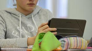 Une adolescente devant les réseaux sociaux sur sa tablette. (MAXPPP)