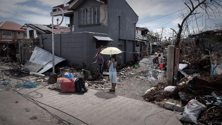 Une enfant devant sa maison détruite par le typhon Haiyan, àTacloban, sur l'île de Leyte (Philippines), le 13 novembre 2013. (PHILIPPE LOPEZ / AFP)