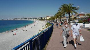 Deux personnes se baladent sur la promenade des Anglais à Nice, le 30 mai 2020. (VALERY HACHE / AFP)
