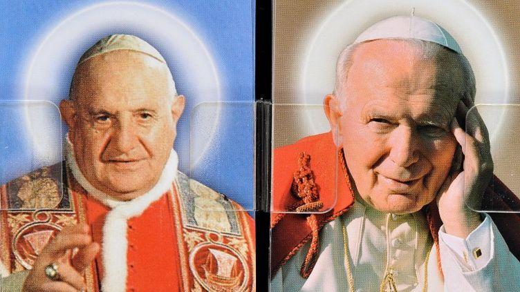 Cette image prise le 21 avril 2014 montre des cartes postales dépeignant le Pape John XXIII et le Pape Jean-Paul II vendu dans un magasin à Rome. ( AFP )