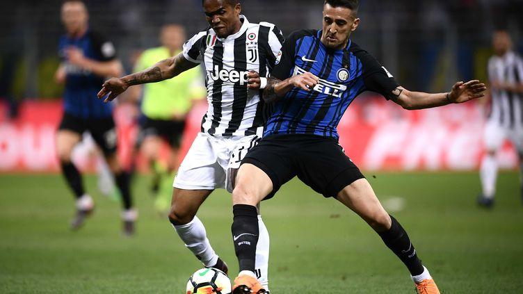 Douglas Costa, auteur du 1er but de la Juventus, ici aux prises avec l'Interiste Vecino. (MARCO BERTORELLO / AFP)