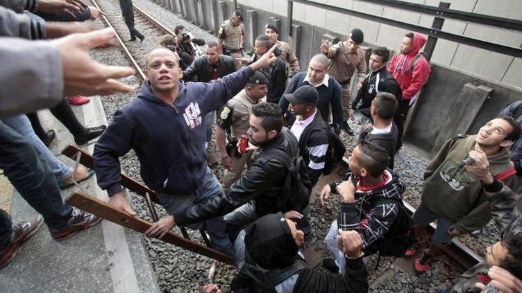 (Des policiers évacuent les voyageurs descendus sur les rails, à São paulo. © REUTERS / Chico Ferreira)