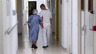 Une résidente accompagné d'un personnel soignant dansd'un Ehpad près de Montpellier (Hérault), le 28 mai 2020. (GUILLAUME BONNEFONT / MAXPPP)