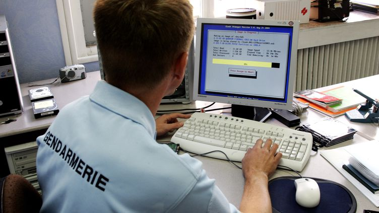 """Un gendarme de la cellule """"cybercriminalité""""copie le disque dur d'un ordinateur afin d'en vérifier le contenu, le 16 septembre 2005 à Lille (Nord). (FRANÇOIS LO PRESTI / AFP)"""